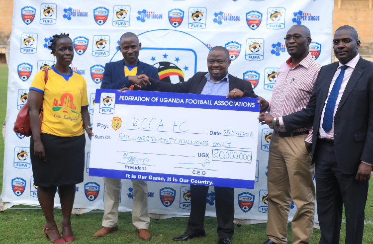 FUFA 1st Vice President Justus Mugisha hands over a 20M dame cheque to KCCA FC official as as FUFA DCEO(R) looks on
